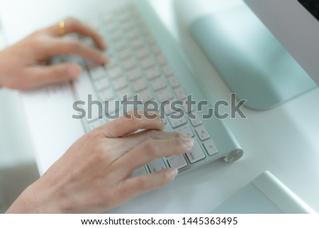 Hands of woman typing on the white modern keyboard or using computer playing social media in coffee shop. #1445363495