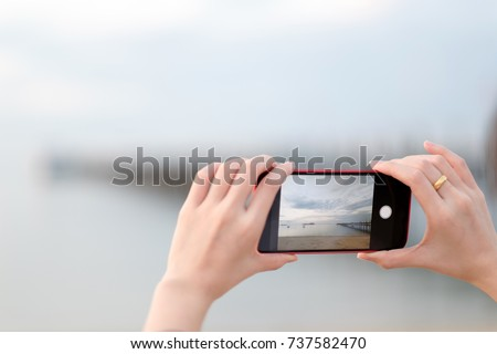 Hands of woman using a smart phone for take a picture with blured background.