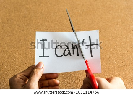 Hands of woman using scissors to remove the word I can't to read I can. Concept for self belief, positive attitude and motivation.