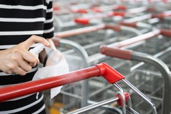 Hands of woman using spraying alcohol antiseptic,disinfecting spray,cleaning on shopping cart,trolley handle,protection during Coronavirus pandemic,Covid-19,wipe clean the surfaces with disinfectant