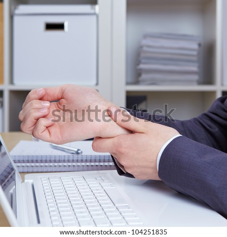 Hands of woman with carpal tunnel syndrome over computer keyboard