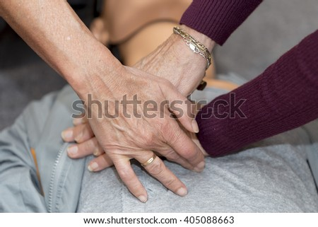 Hands of women are seen on a mannequin during an exercise of resuscitation #405088663