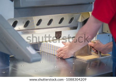 Hands of worker working on cutter guillotine machine in a printing factory
