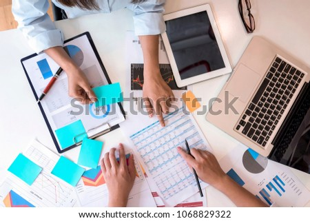 Hands of young businesspeople pointing at business graph report  on tablet in the office,top view