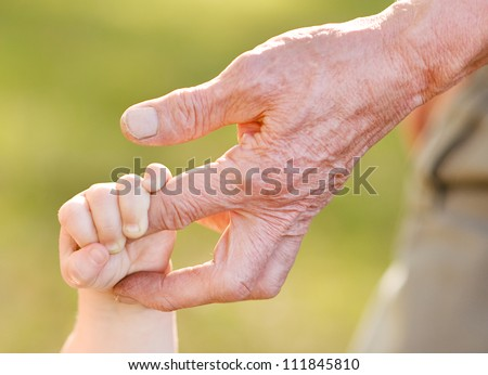 hands of young child and old man