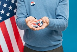 Hands of young contemporary businessman showing group of vote insignias while standing against stars-and-stripes background
