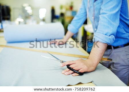 Hands of young tailor with scissors on light grey fabric spread on table