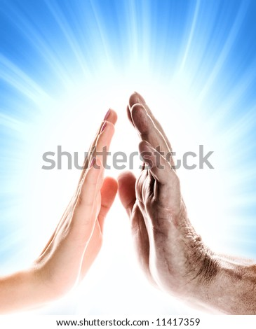 Hands of young woman and elderly man over abstract blue background