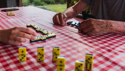 Hands of young woman and old man while playing dominoes