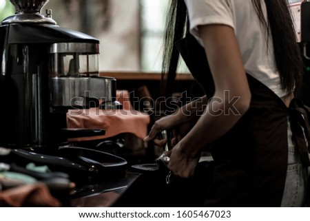 Hands of young woman barista woman barista press ground coffee into portafilter to make espresso hot drink. Coffee making cafe barista concept, Small business owner and work concept.