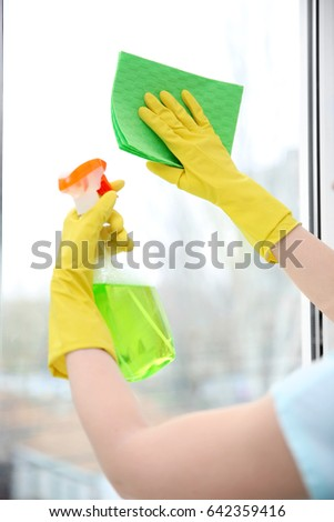 Hands of young woman cleaning window #642359416