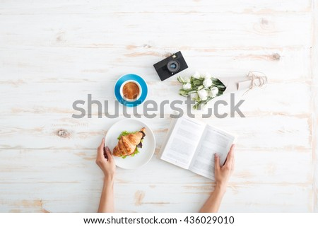 Hands of young woman eating croissant with coffee and reading book on wooden table with flower bouquet and photo camera