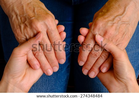 Hands of young woman holding hands of an elderly woman, top view