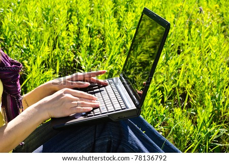 Hands of young woman on laptop outdoor. Sunny summer day.
