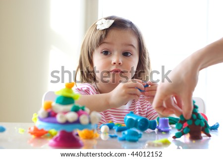 Hands of young woman show little girl how to use play dough
