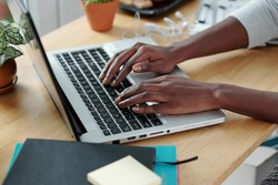 Hands of young woman typing on laptop when working at office desk at home