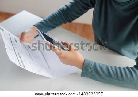 Photo of  hands of young woman using mobile smart phone for scan and payment online with family budget cost bills on desk in home office, plan money cost saving, investment, business finance, expenses concept