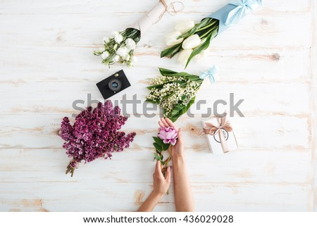 Hands of young woman with flower bouquets, gift box and photo camera on wooden table