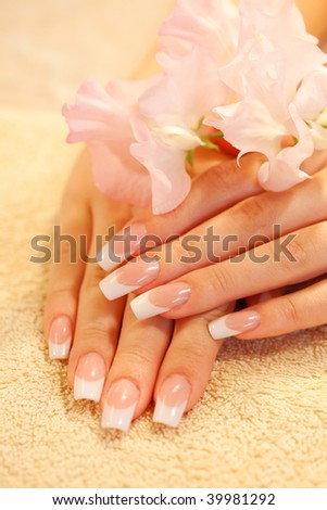 Hands of young woman with french manicure on the towel