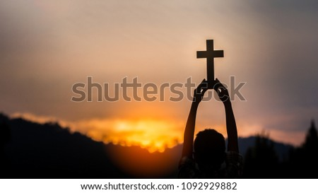 hands off children holding christian cross with light sunset background,christian concept.
