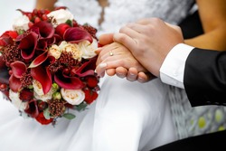 Hands oHands of newlyweds with wedding rings and a wedding bouquetf newlyweds with wedding rings and a wedding bouquet