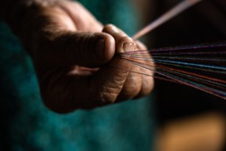 hands on a loom with thread