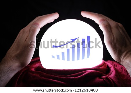Hands on a magic crystal ball which is showing a financial forecast #1212618400