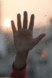 Hands on a raindrop window .Human hands on water drop window glass.Hands are trying to reach for help.