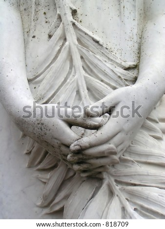 Hands on a statue in a cemetery
