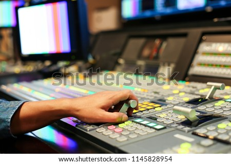 Hands on dissolve of Switcher buttons in studio TV station, Audio and Video Production Switcher of Television Broadcast.