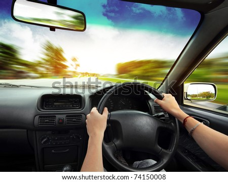 Hands on steering wheel of a car and blurred asphalt road