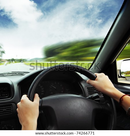 Hands on steering wheel of a car and motion blurred asphalt road and sky