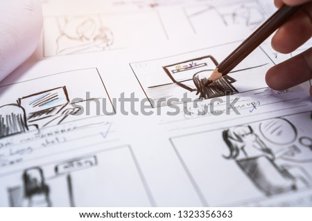 Hands on Storyboard movie layout for pre-production, storytelling drawing creative for process production media films. Script video editors and writing graphic in form displayed in maker shooting