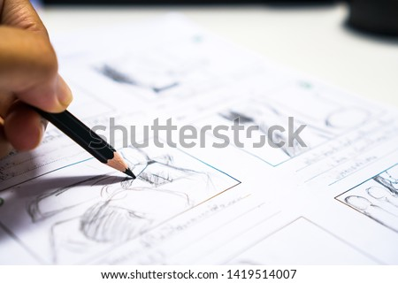 Photo of  Hands on Storyboard movie layout for pre-production, storytelling drawing creative for process production media films. Script video editors and writing graphic in form displayed in maker shooting