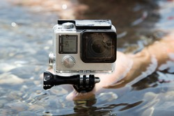 Hands on water with camera GoPro
