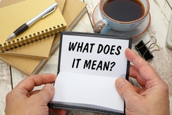 Hands open a notebook with the inscription What Does It Mean on the background of the office desk