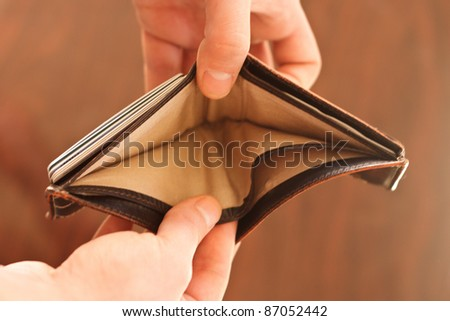 Hands opening an empty wallet against blurred background