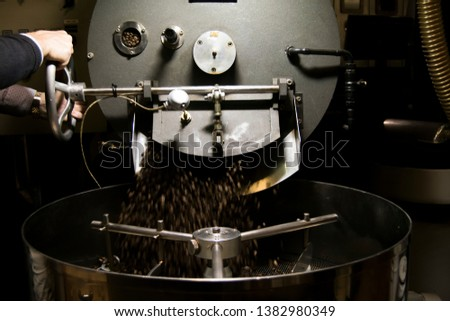 hands opening the coffee roaster machine making falling the roasted coffee beans. Picture taken from a frontal perspective.