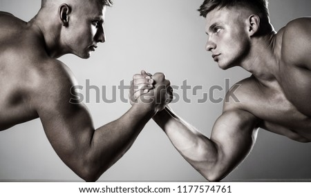 Hands or arms of man. Muscular hand. Two hands. Muscular men measuring forces, arms. Two men arm wrestling. Rivalry, closeup of male arm wrestling. Hand wrestling, compete. Black and white.