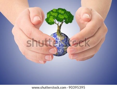 Hands, our planet Earth and the tree