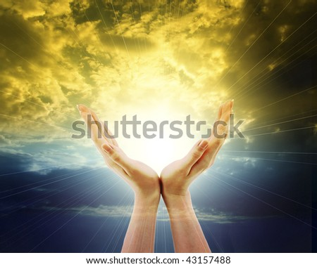 hands outstretched towards shining sun and sky