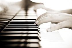 Hands over piano in beautiful sepia tone.