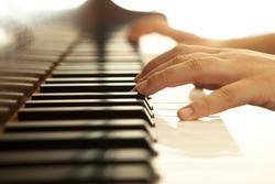 Hands over piano in warm tones.