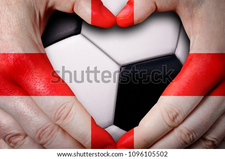 Hands painted with an England flag forming a heart over soccer ball background #1096105502