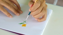 Hands painting watercolor artwork of beautiful yellow flower and green leaf by brush on paper Concept of art, freedom activity, creative learning.