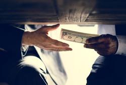 Hands passing money under table corruption bribery