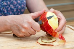 Hands peeling a cooking apple on a wooden board