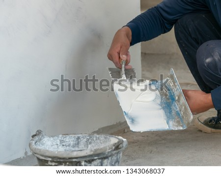Hands Plasterer at work. Application of the plaster on the wall in construction site #1343068037