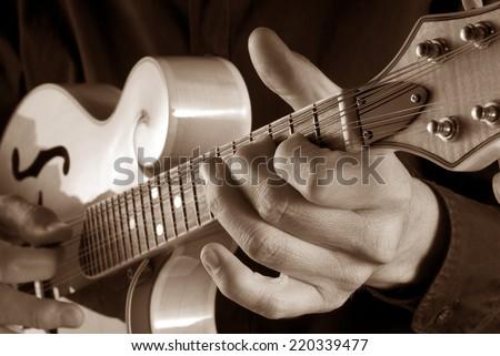 hands playing a classic bluegrass mandolin,sepia image