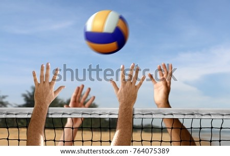 Hands playing beach volleyball
